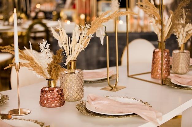 Tabel instelling op een luxe bruiloft en mooie bloemen op tafel. bruiloft decor, bloemen, roze en gouden decor, kaarsen. feestelijk tafeldecor.