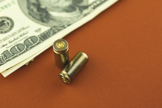 Tabel met dollars en kogels voor een pistool, pistoolpatroon met geld, misdaad en corruptie concept achtergrondfoto
