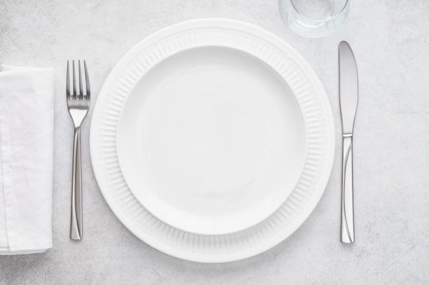 Tabel met lege witte plaat, glas, servet, vork en mes