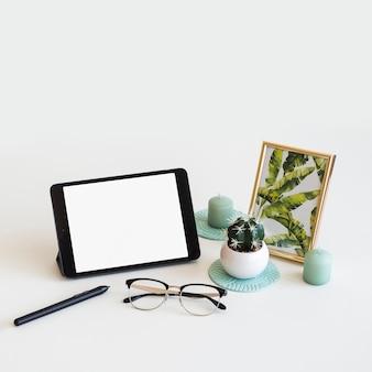 Tabel met tablet in de buurt van fotolijst, pen en bril