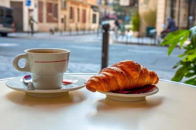 Tabel van straatcafé in parijs in de ochtend. kopje koffie en croissants close-up. achtergrond in defocus