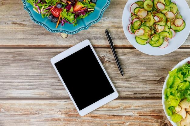 Tablet en diverse salades op houten tafel