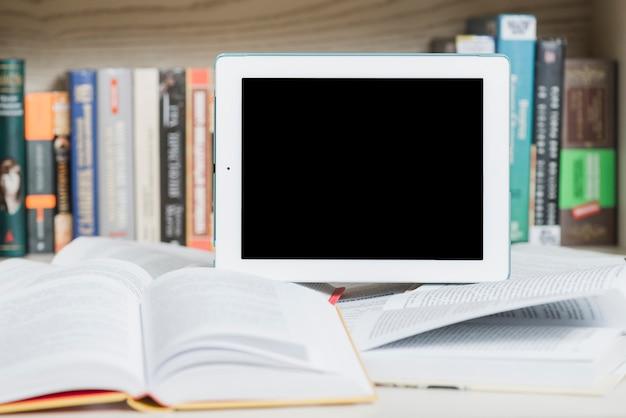 Tablet en geopende boeken in de buurt van boekenkast