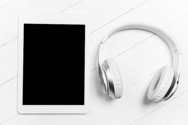 Tablet en koptelefoon. leeg scherm. monochroom stijlvolle en trendy compositie in witte kleur op studio achtergrond. bovenaanzicht, plat gelegd. pure schoonheid van de gebruikelijke dingen in de buurt.