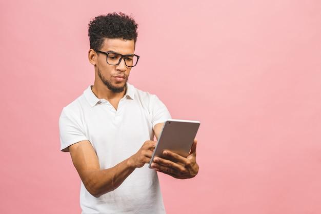 Tablet gebruiken. de jonge knappe afrikaanse tablet van de mensenholding en het spelen van spelen of het gebruiken van het boeken app geïsoleerd tegen roze muur.