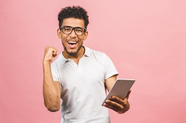 Tablet gebruiken. gelukkige winnaar! jonge knappe afrikaanse mens die holdingstablet glimlachen en spelen of een boeking app gebruiken die tegen roze muur wordt geïsoleerd.