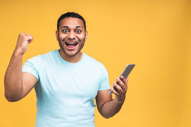 Tablet gebruiken. gelukkige winnaar! jonge knappe afro-amerikaanse indiase man glimlachend tablet te houden en spelletjes te spelen of met behulp van een boeking app geïsoleerd op gele achtergrond.