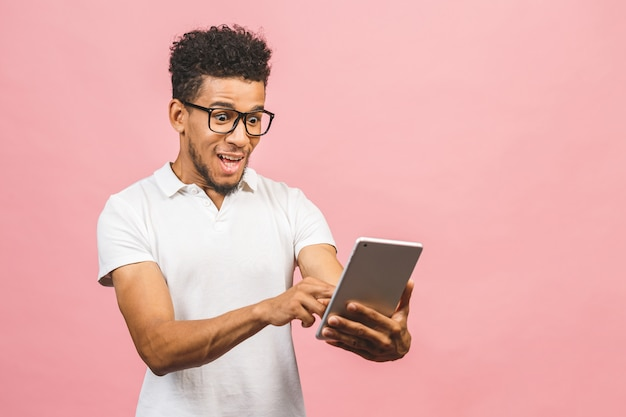 Tablet gebruiken. jonge knappe afrikaanse mens die holdingstablet glimlachen en spelen of een boeking app gebruiken die tegen roze muur wordt geïsoleerd.
