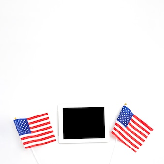Tablet geplaatst tussen amerikaanse vlaggen
