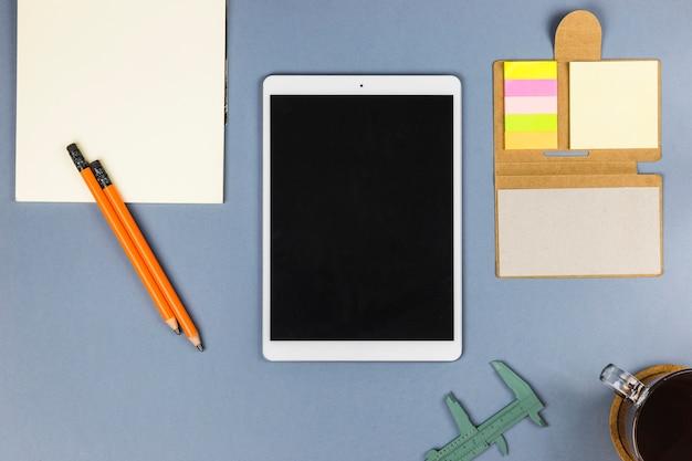 Tablet in de buurt van papier, beker, schuifmaat en stickers