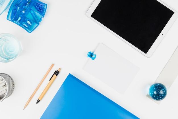 Tablet in de buurt van papier, speelgoed bal, potlood, pen en clips