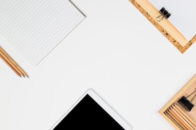 Tablet in de buurt van papieren, potloden en clips