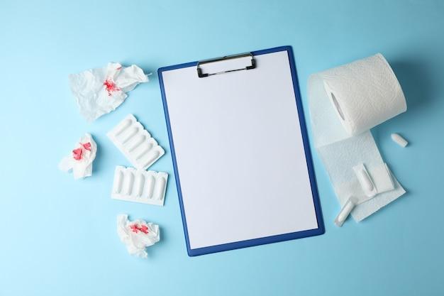 Tablet, kaarsen en wc-papier op blauw, ruimte voor tekst