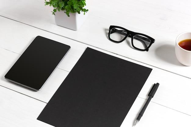 Tablet leeg blad glazen en koffiekopje op kantoor houten tafel