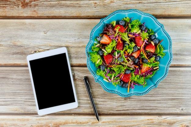 Tablet met gezonde salade voor food blogger