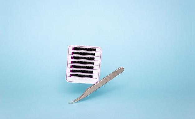 Tablet met kunstwimpers en pincet voor wimperverlenging