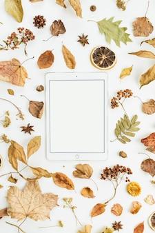Tablet met leeg scherm met droge herfstbladeren, bloemblaadjes en sinaasappels op wit oppervlak