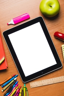 Tablet met leeg scherm met schoolbenodigdheden op tafel, bovenaanzicht