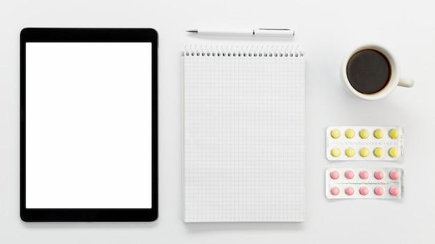 Tablet met notebook en pillen