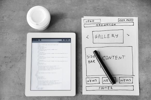 Tablet met programmeercode voor website op tafel