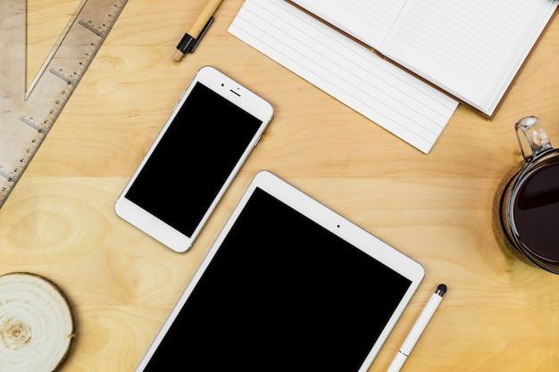 Tablet met smartphone met notitieboekje op houten lijst