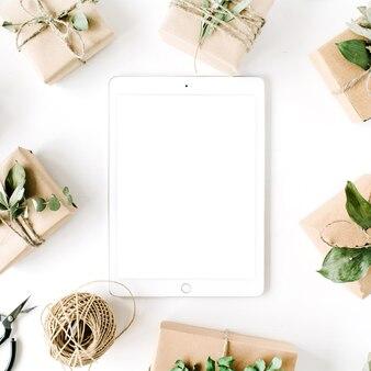 Tablet met tabletscherm en schoonheidsregeling frame van ambachtelijke dozen en groene takken op witte achtergrond.