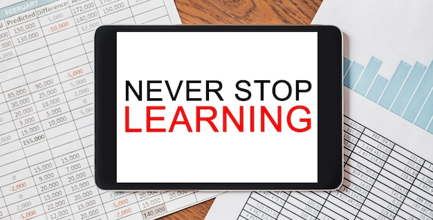 Tablet met tekst never stop learning op je desktop met documenten, rapporten en grafieken. zakelijk en financieel concept