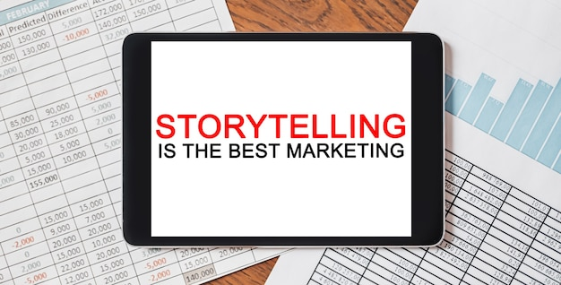 Tablet met tekst storytelling is de beste marketing op je desktop met documenten, rapporten en grafieken. zakelijk en financieel concept