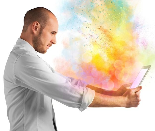 Tablet met uitbarsting van heldere kleurrijke poeders