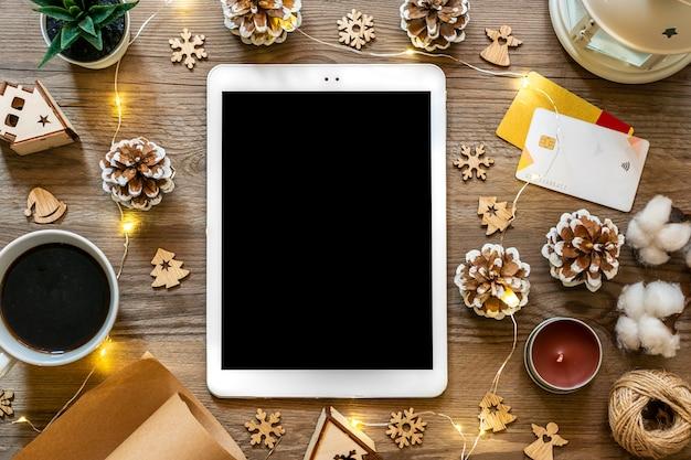 Tablet met zwart scherm, kopje koffie, pinpas, xmas decor, sneeuwvlokken op houten tafel