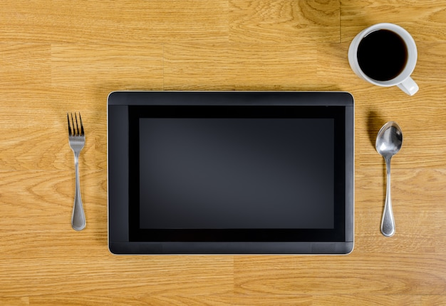 Tablet over houten tafel met lepel, vork en koffiekopje