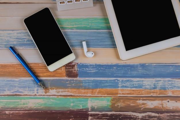 Tablet, telefoon, draadloze koptelefoon en pen op de tafel.