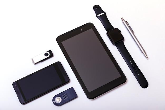 Tablet, telefoon, pendrive, pennen, horloge op wit