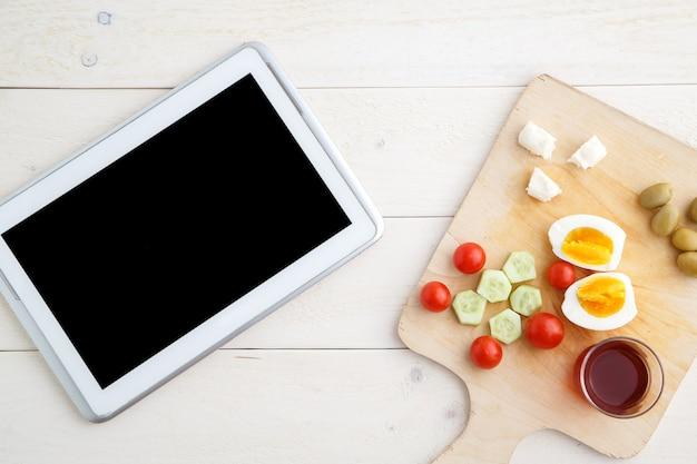 Tablet, thee en turks, mediterraan ontbijt op een licht houten dienblad