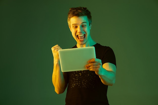 Tablet vasthouden, winst in weddenschap of spel vieren. blanke man portret op groene studio achtergrond in neonlicht. prachtig mannelijk model. concept van menselijke emoties, gezichtsuitdrukking, verkoop, advertentie.