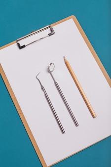 Tablet voor records op een blauwe achtergrond met tandheelkundige instrumenten