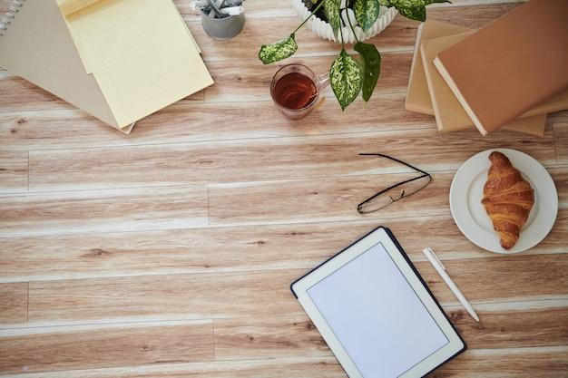 Tabletcomputer met leeg scherm, boeken, croissants en glazen op tafel, van bovenaf bekijken