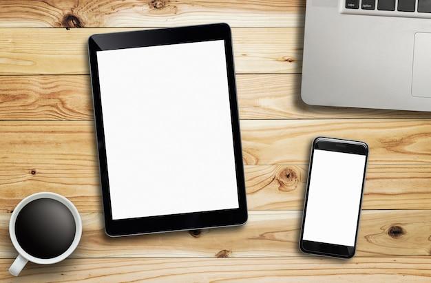 Tabletlaptop koffie van kop en smartphone op houten lijst.