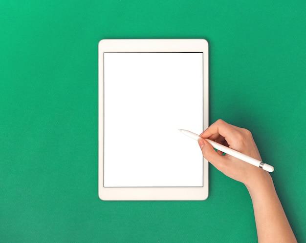 Tabletonderwijs en applicatiemodel met leeg wit scherm en vrouwenhand met styluspotlood, groene kantoorwerkruimteachtergrond, bovenaanzicht en kopieerruimtefoto