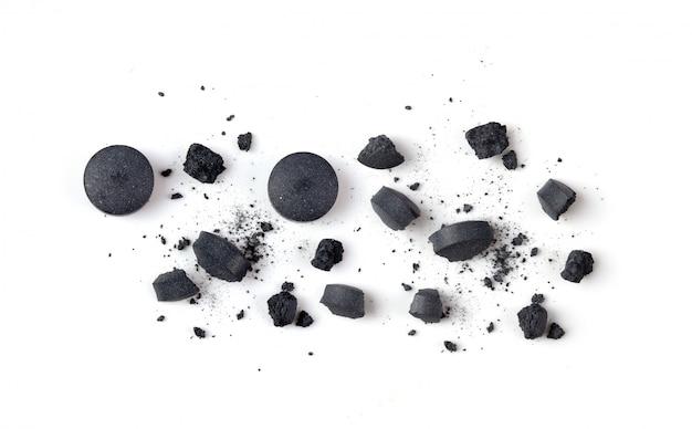 Tabletten geactiveerde houtskool en poeder op wit.