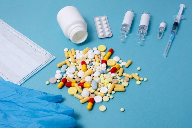 Tabletten, vaccin, spuit-thermometer op een blauwe tafel het concept van bescherming tegen virussen. vlakke styling, bovenaanzicht, kopieerruimte