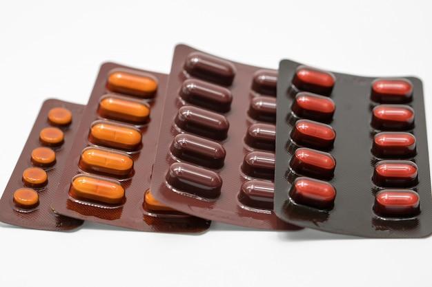 Tablettenpillen in bruin blaarpak op witte achtergrond. lichtbestendige medicijnverpakking. farmaceutische industrie. apotheek achtergrond. geneeskunde moet vermijden van licht. farmaceutische producten.