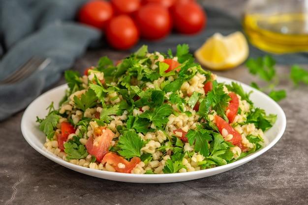 Tabouleh-salade met bulgur, peterselie, bosui en tomaat in kom op grijs.