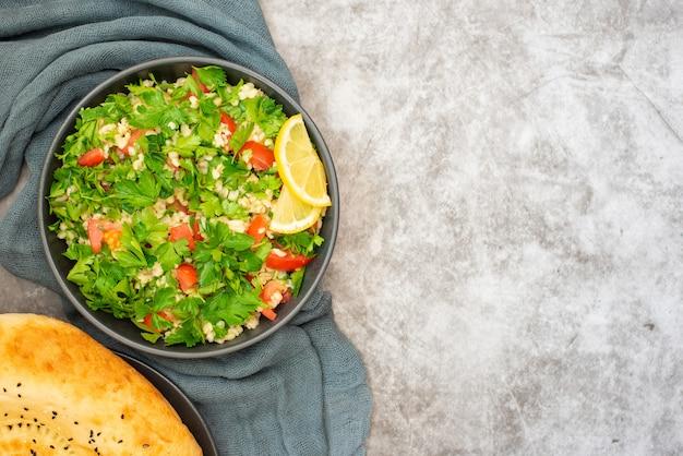 Tabouleh-salade met bulgur, peterselie, lente-ui en tomaat in kom op grijze achtergrond. bovenaanzicht. met kopie ruimte