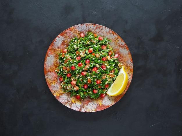 Tabouleh salade met couscous in een kom op de zwarte tafel. levantijnse vegetarische salade met peterselie, munt, bulgur, tomaat.