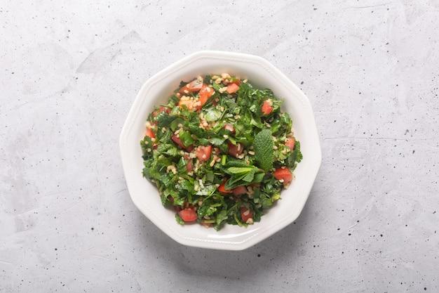 Tabouleh salade, traditioneel midden-oosten of arabisch gerecht. meestal bereid met peterselie, munt, bulgur, tomaat. concrete rustieke achtergrond
