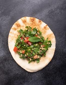 Tabouleh salade, traditioneel midden-oosten of arabisch gerecht, op pitabroodje. meestal bereid met peterselie, munt, bulgur, tomaat