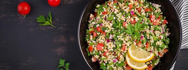 Tabouleh salade. traditionele midden-oosterse of arabische schotel. levantijnse vegetarische salade met peterselie, munt, bulgur, tomaat. banner.
