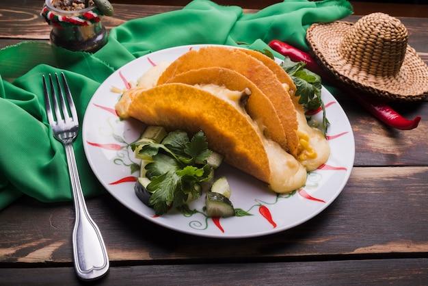 Taco onder groenten op schotel dichtbij spaanse peper en sombrero met servet