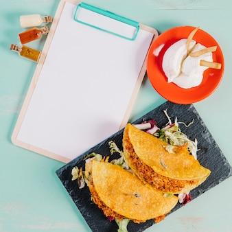 Taco's en specerijen in de buurt van klembord